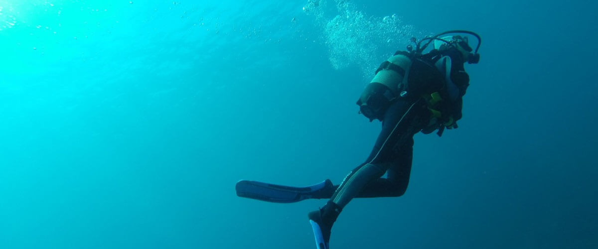 diver swimming through blue ocean with wetsuit and diving gear blowing bubbles