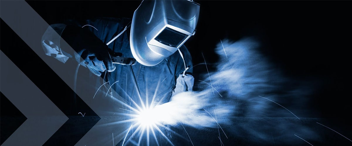 welder welding in the dark with blue sparks flying and smoke