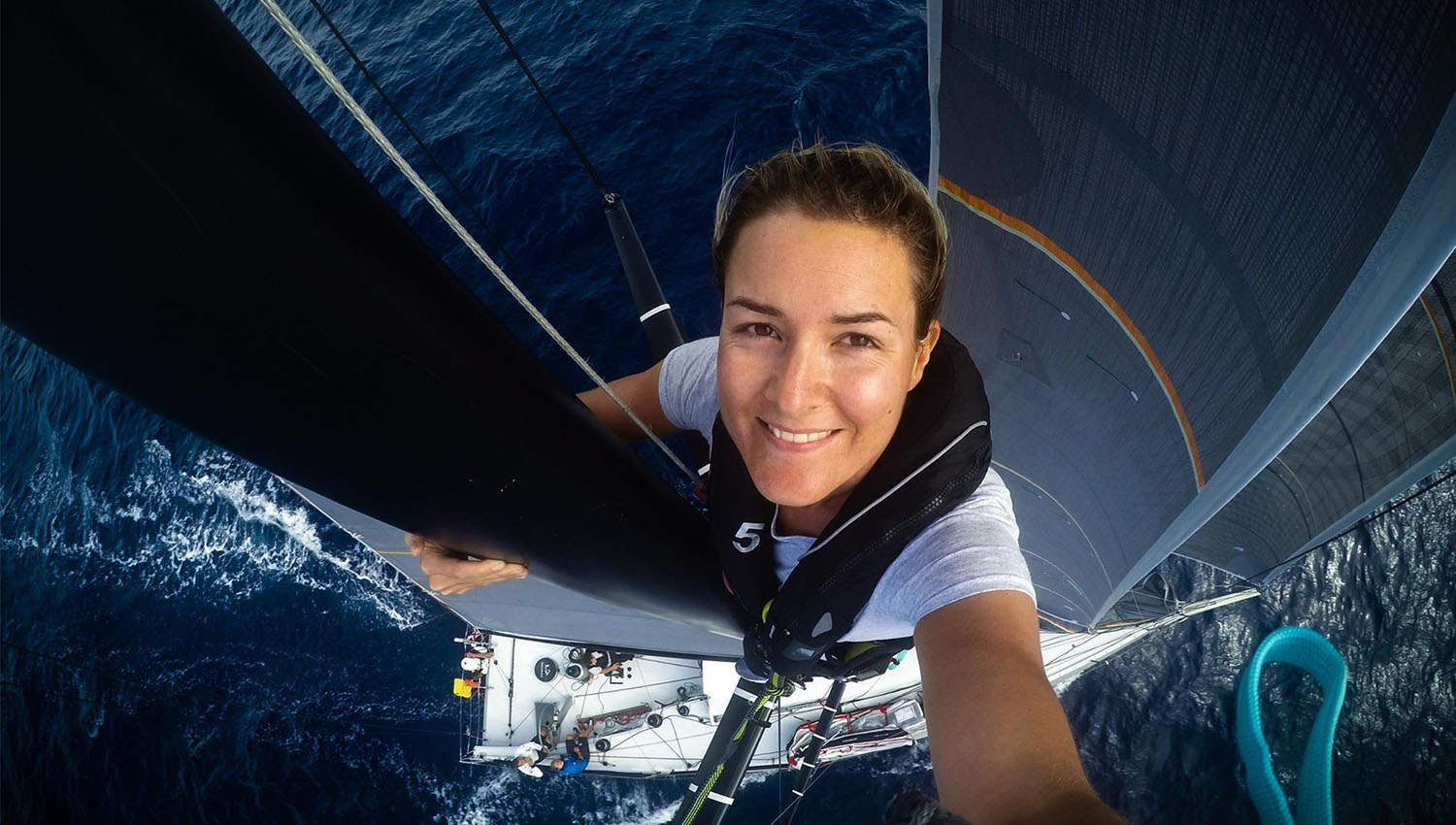 woman on mast with birds eye view of sail boat and ocean